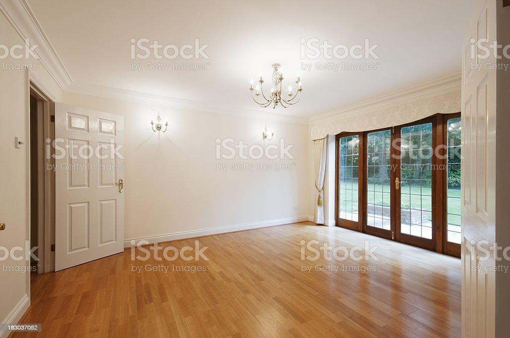 Empty wooden floored room with patio doors to garden royalty-free stock photo