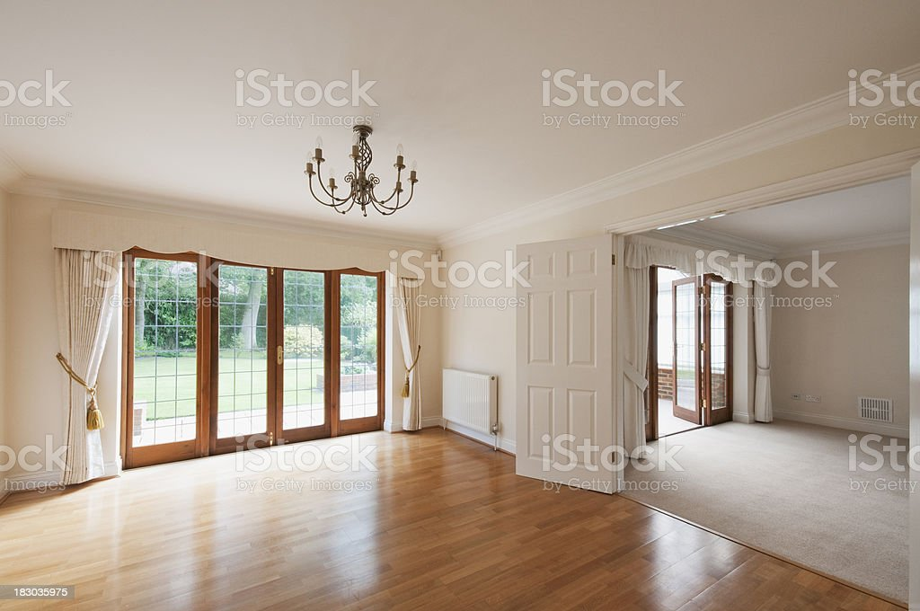 Empty wooden floored rooms with patio doors to garden stock photo