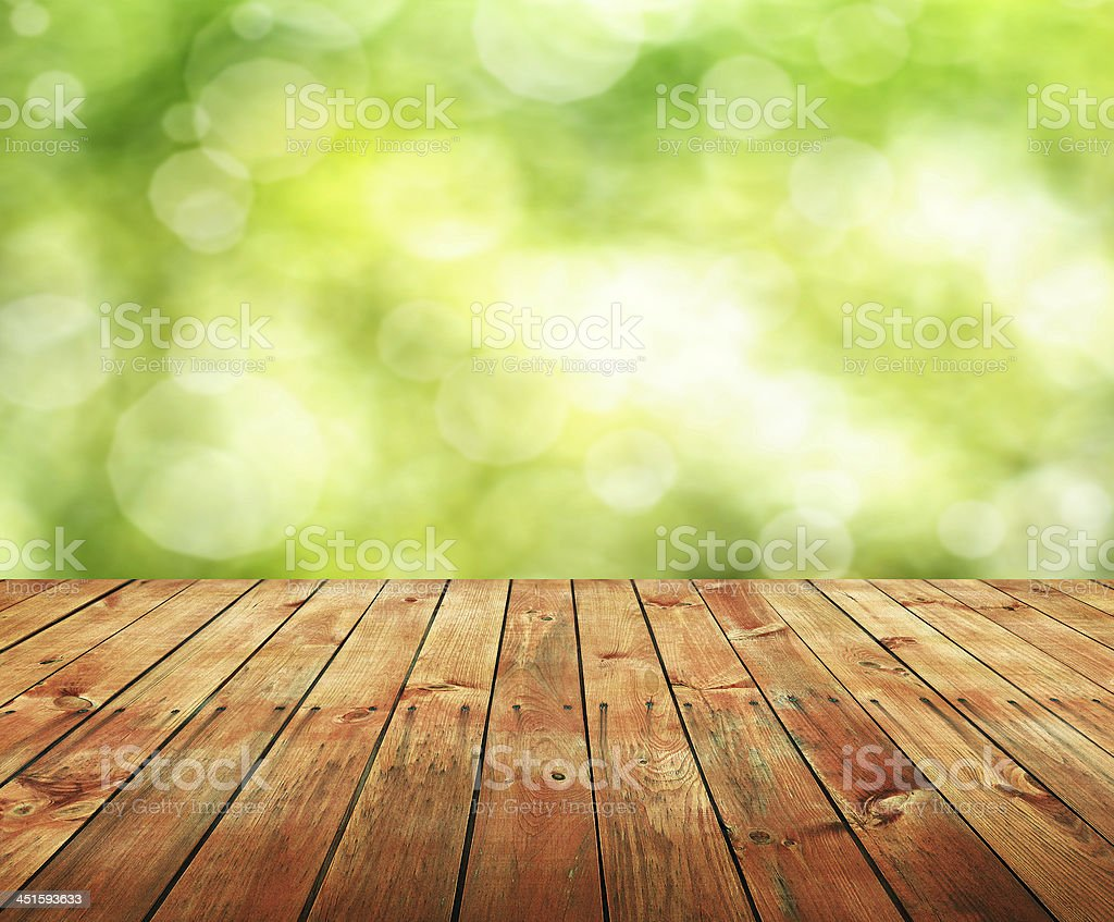 Empty wooden panel table with blurred green background royalty-free stock photo