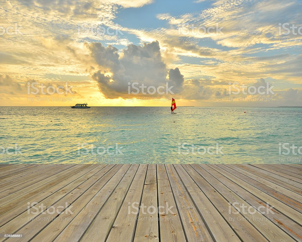 Empty wooden pier beside sea with sunset stock photo