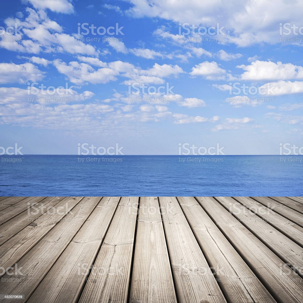 Empty wooden pier with sea and cloudy sky on background stock photo