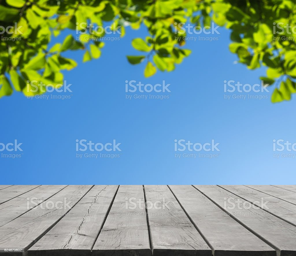 Empty wooden platform and green leaves defocused abstract background stock photo
