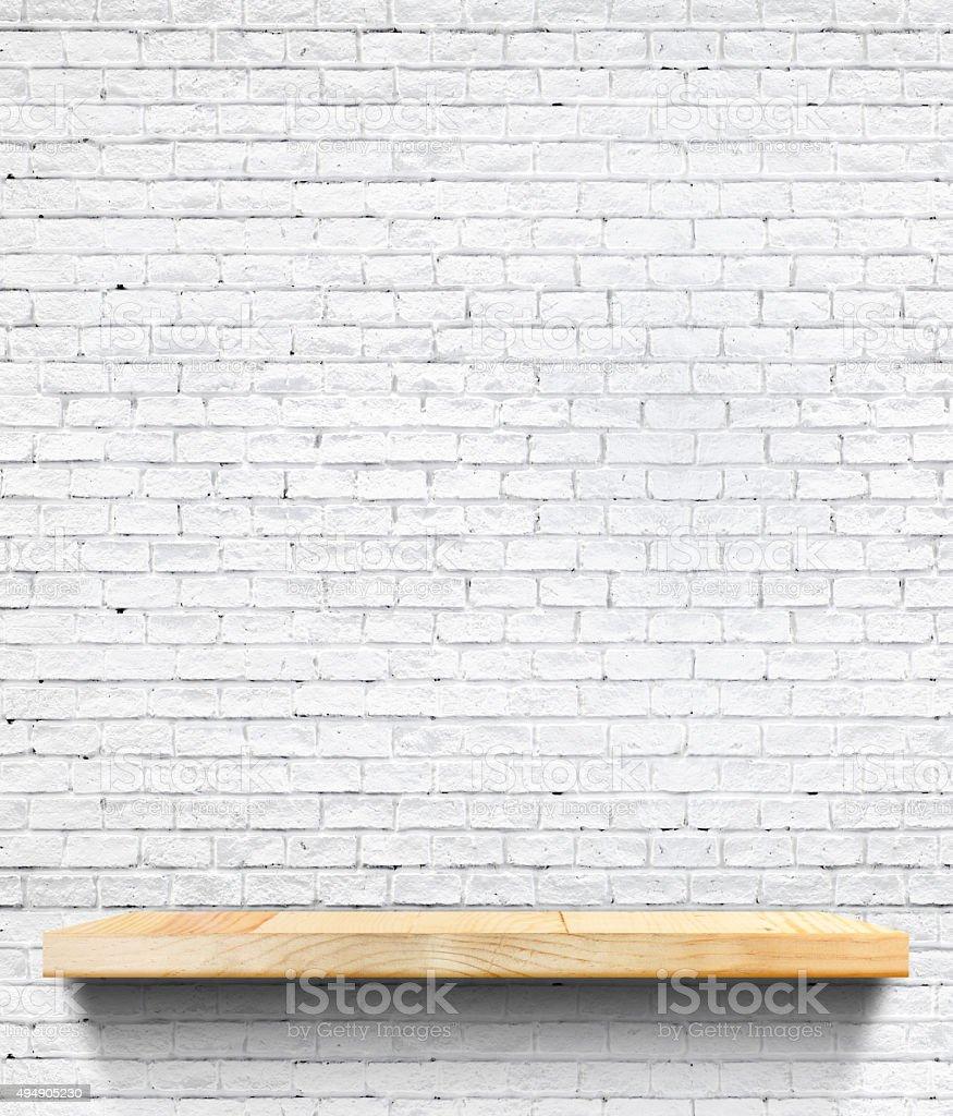 Empty Wooden shelf at white tile ceramic wall stock photo
