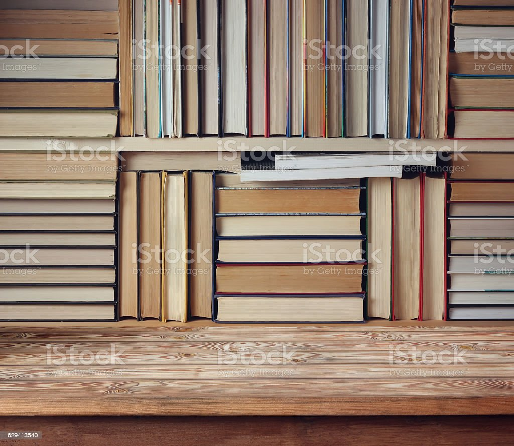 Empty wooden table against the background of the books. stock photo