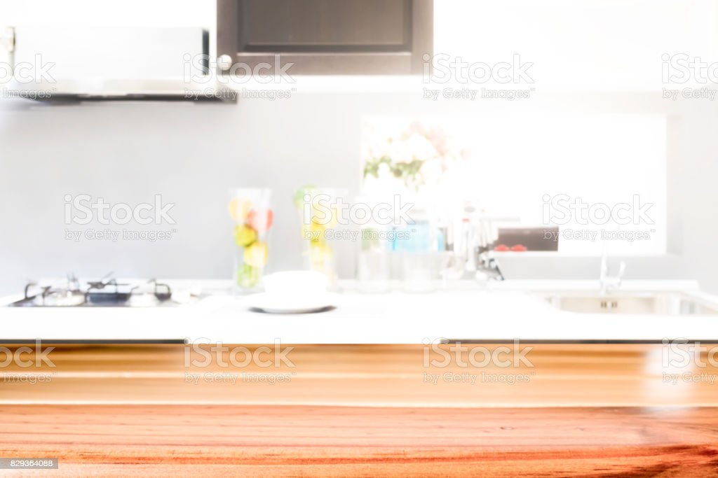 Empty wooden table and blurred kitchen background for display or...
