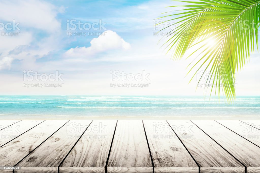 Empty wooden table and palm leaves with party on beach blurred background in summer time. stock photo