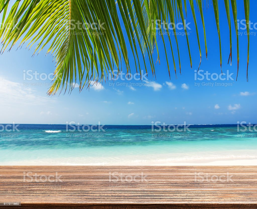 Empty wooden table beside tropical beach stock photo