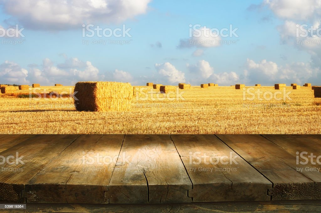 empty wooden table in front of gold wheat haystacks field stock photo