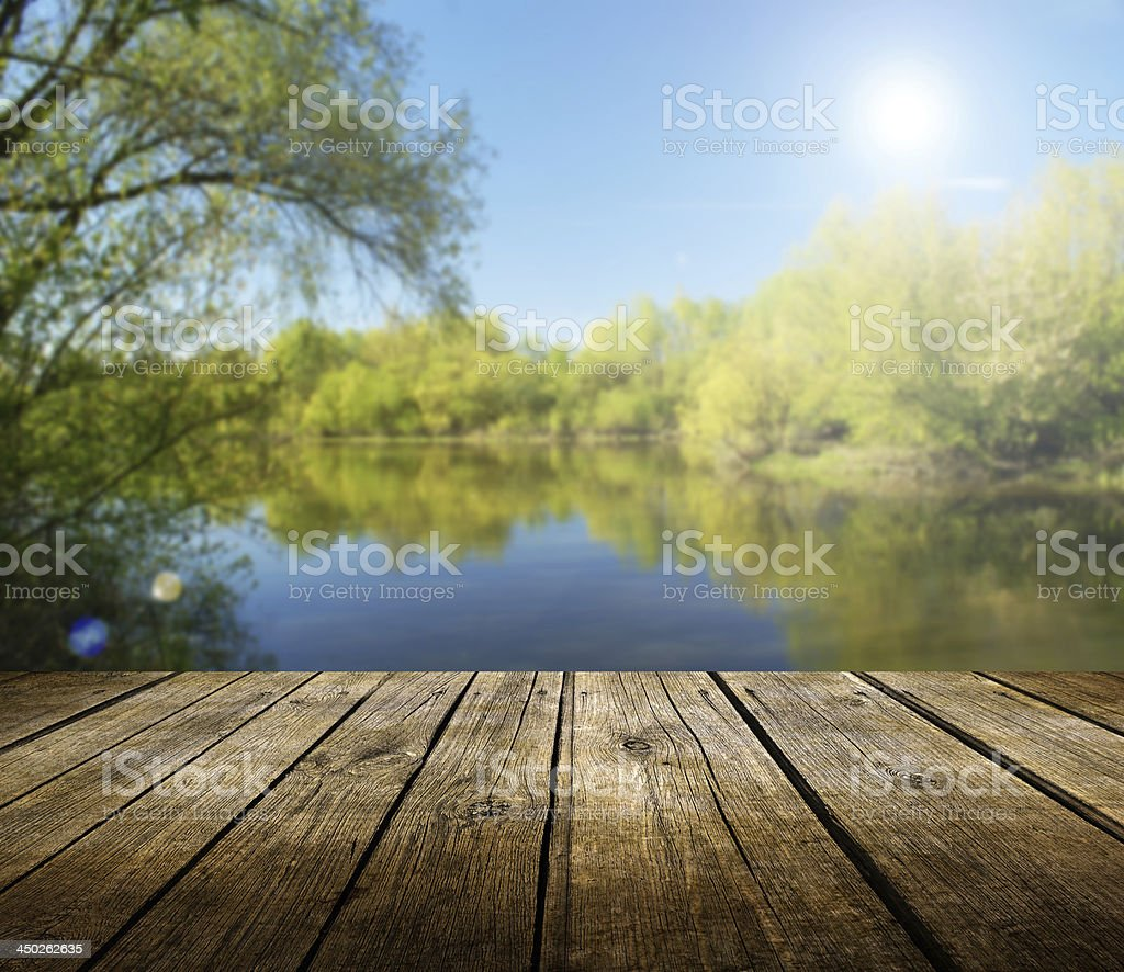 Empty wooden table near lake surrounded by trees stock photo