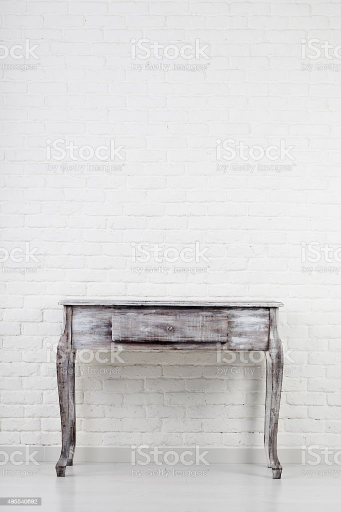 Empty wooden table over white brick wall stock photo