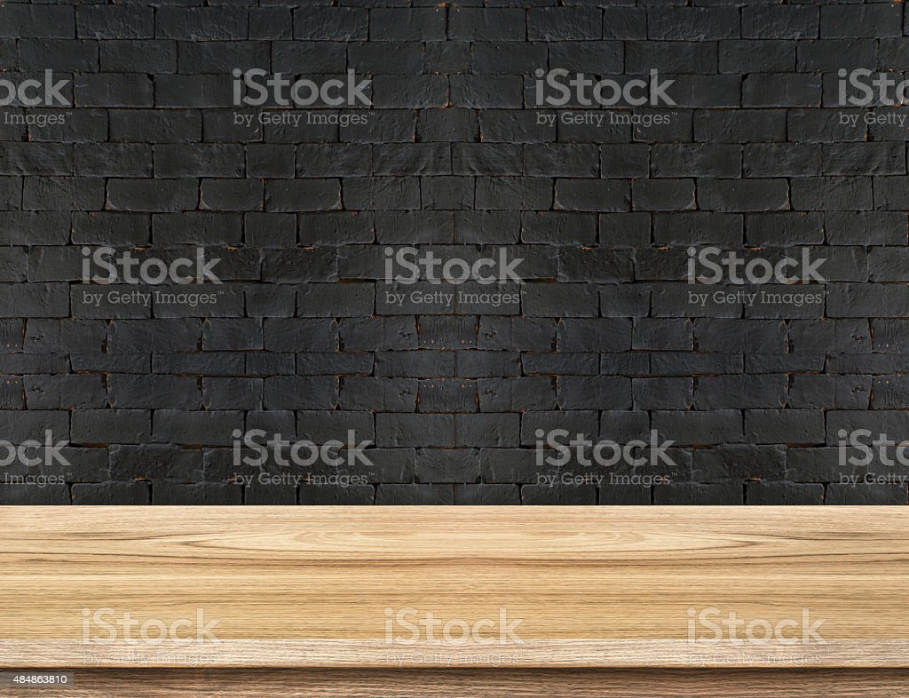 Empty Wooden Table top at black brick wall stock photo