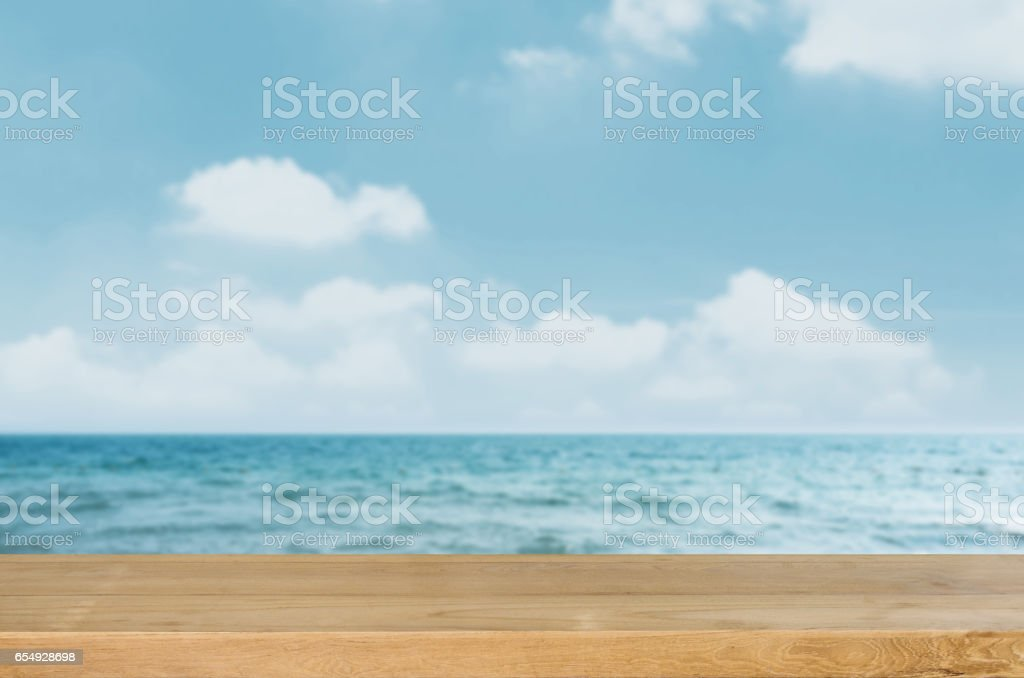 Empty wooden table top with blurred sea and sky background. stock photo