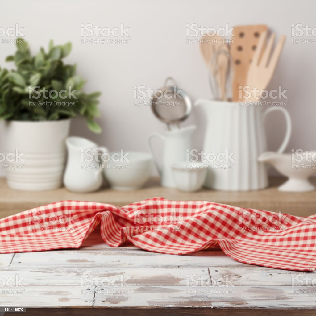 Empty wooden table with red checked tablecloth over kitchen shelf...