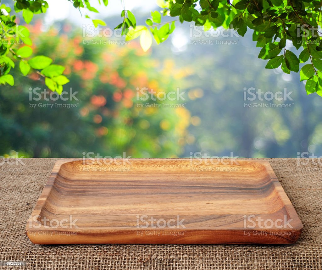Empty wooden tray on table over blur trees  background stock photo