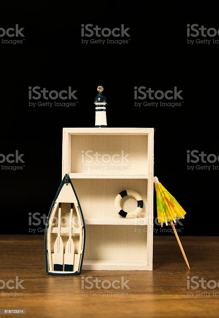 Empty wooden white shelf decorated with boat, lighthouse and lifebuoy stock photo