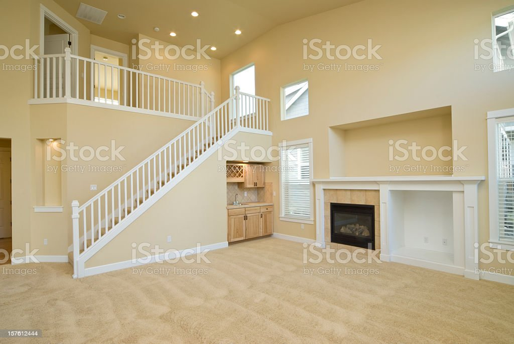 Empty yellow living room with a staircase to a second level royalty-free stock photo