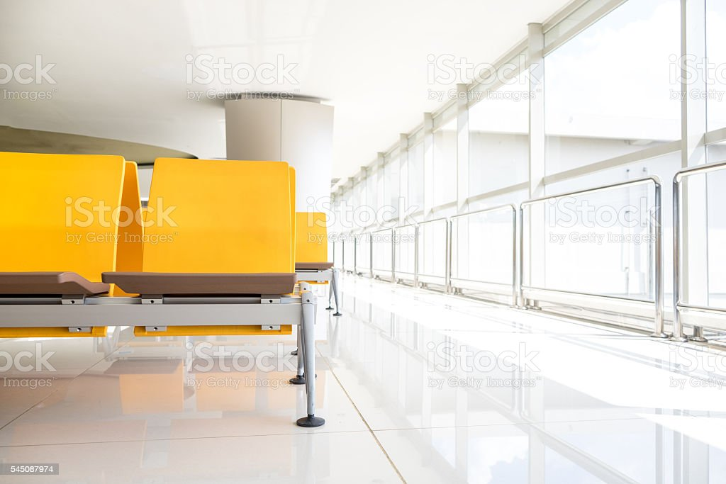 Empty yellow plastic seats near windows on airport terminal. stock photo