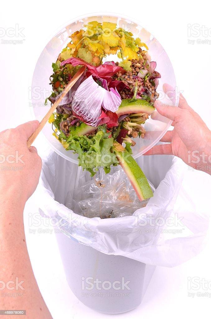Emptying Leftover Food Scraps into a Rubbish Bin stock photo