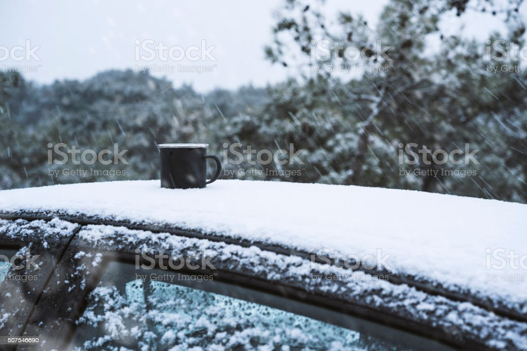 Enamel mug on the car roof in a snowy day stock photo