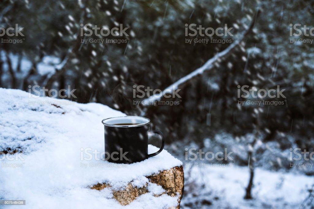 Enamel mug on the rock in a snowy day stock photo