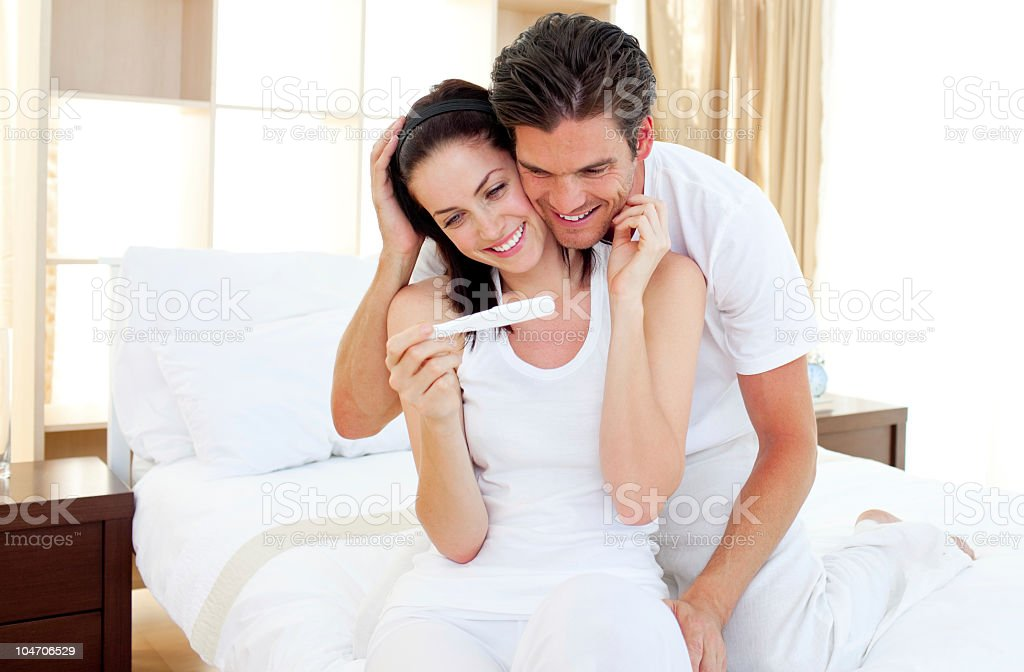 Enamored couple finding out results of a pregnancy test stock photo
