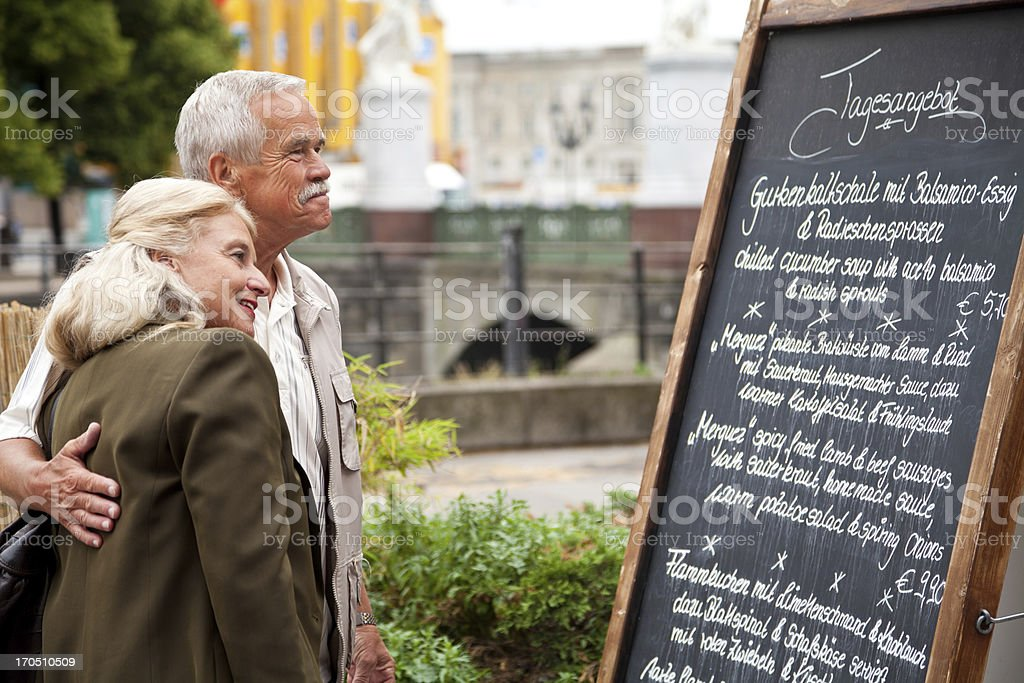 Enamored senior couple in front of restaurant board with menu stock photo