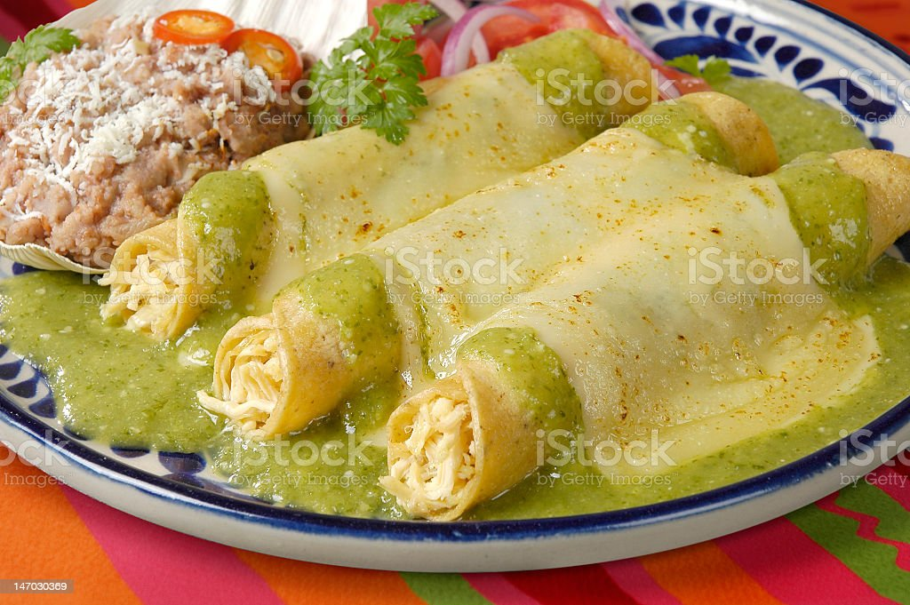 Enchiladas filled with cheese and covered in green sauce stock photo