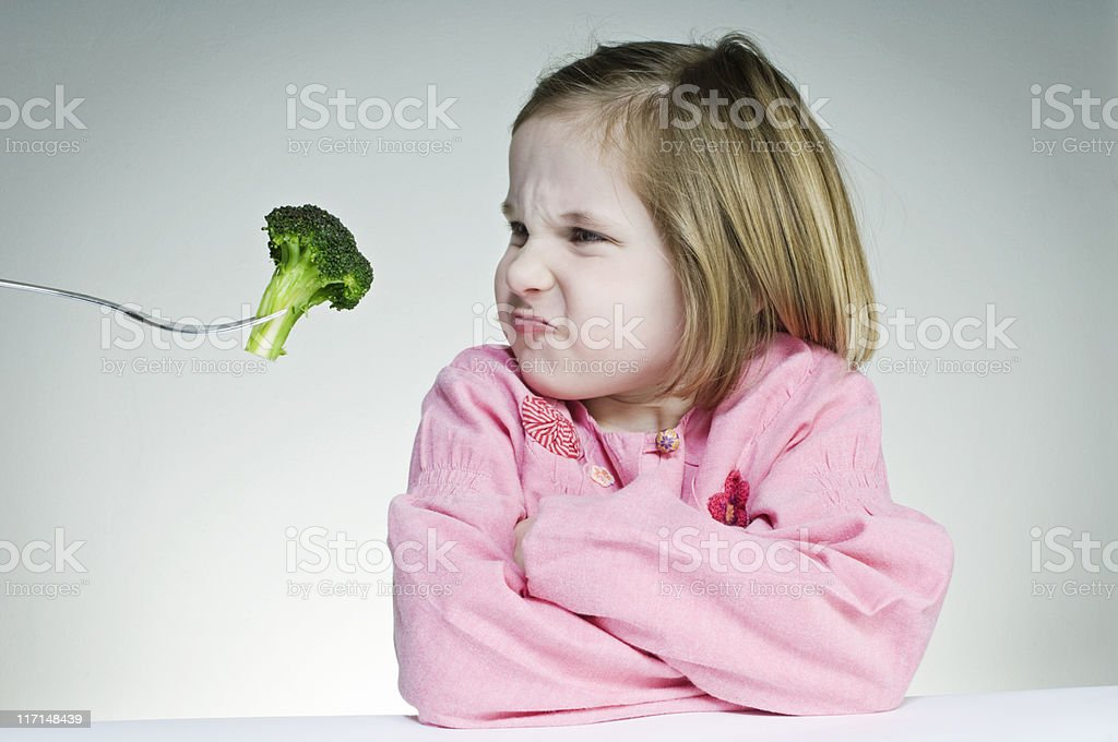Encouraging Young Girl To Eat Her Greens stock photo
