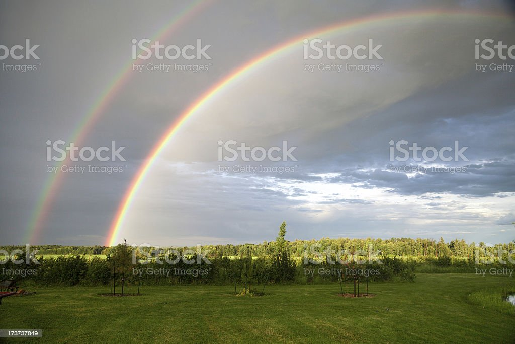 End of a double rainbow in country fields royalty-free stock photo