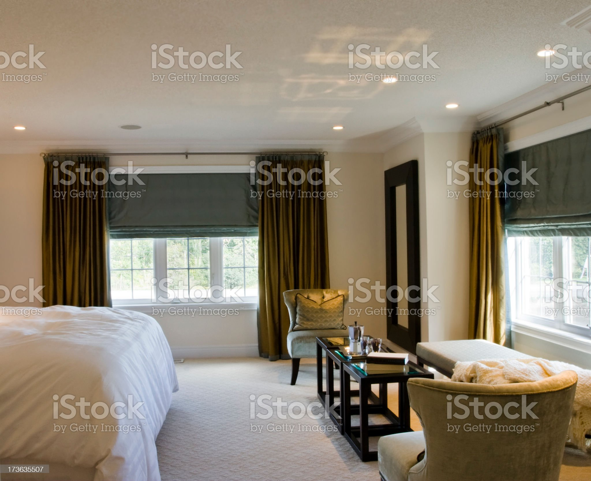 End of bed side view of a modern bedroom with large windows  royalty-free stock photo