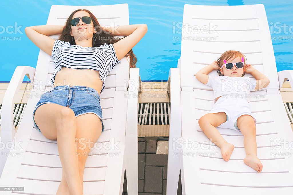 Endless summer! Cute baby and mother relaxing at sunbed stock photo