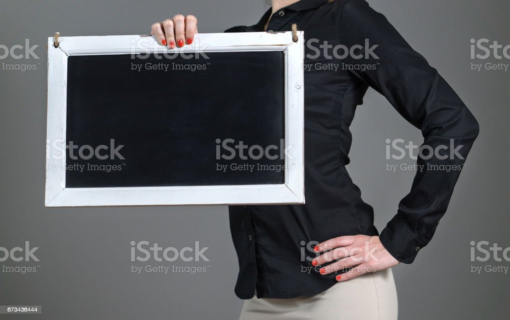 Energetic and sporty young girl holding chalkboard with one hand. Business woman or waitress in a restaurant with black collared shirt. Free blank empty copy space for text. stock photo