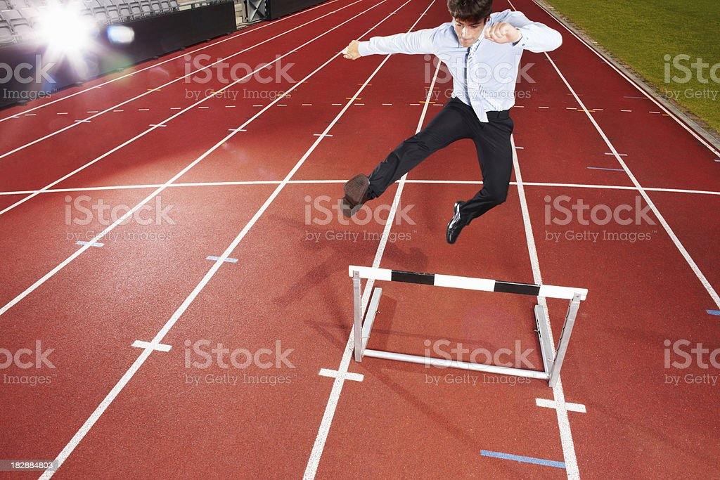 Energetic businessman is jumping over the hurdle with camera flas royalty-free stock photo