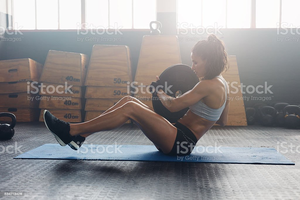 Energetic woman doing abdominal exercise stock photo