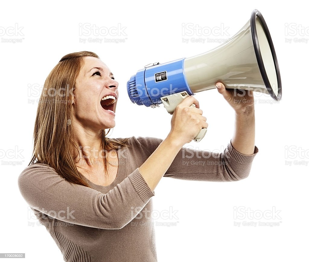 Energetic young beauty yells into loud hailer enthusiastically stock photo