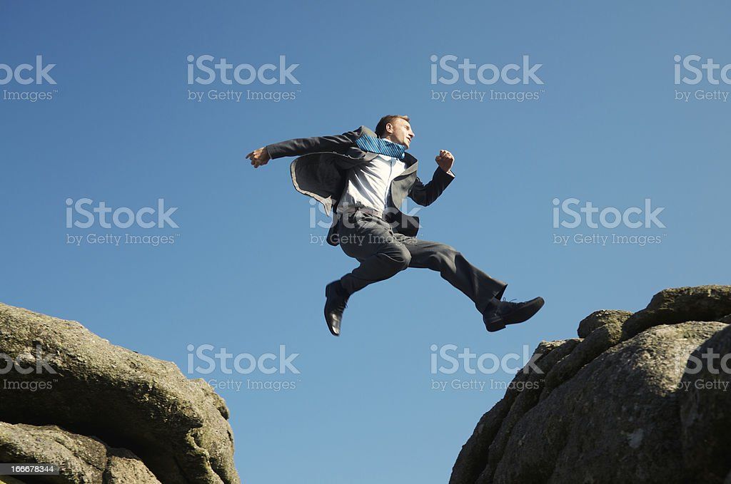 Energetic Young Man Businessman Jumping into Blue Sky between Rocks stock photo