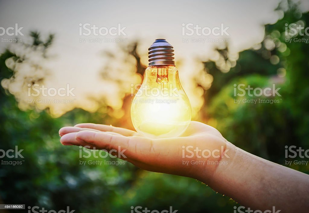 Energy light bulb from sunset on hand concept stock photo