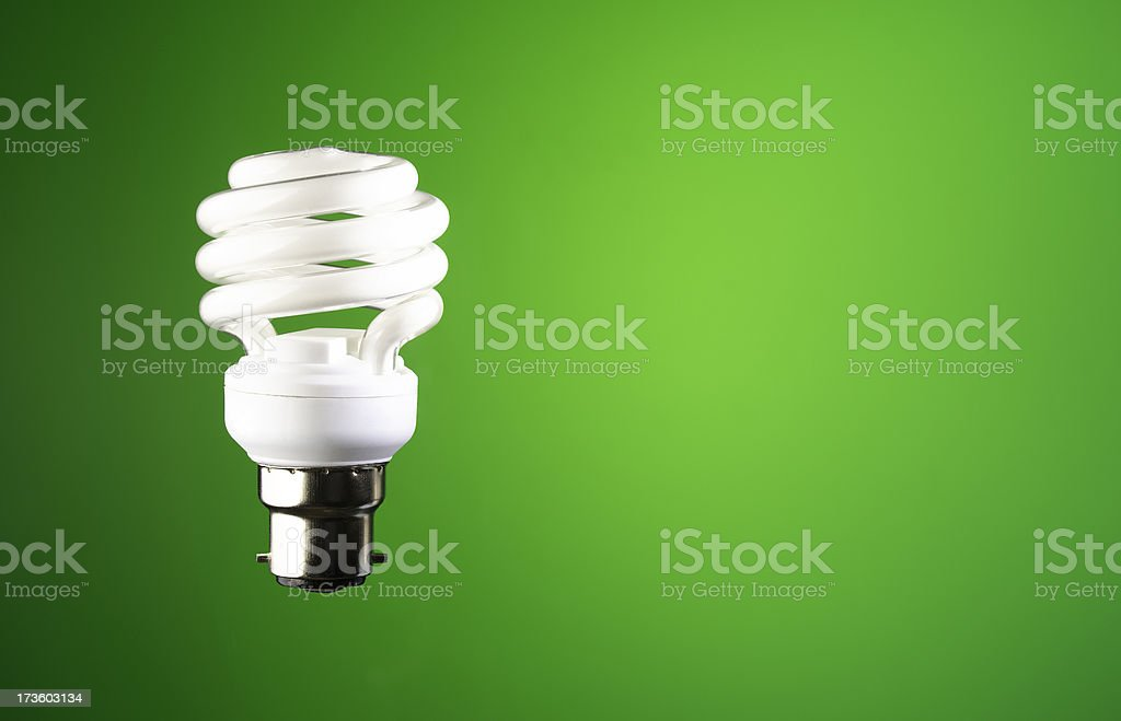 energy saving bayonet fit lightbulb on green royalty-free stock photo