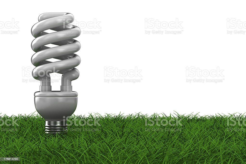 energy saving bulb on grass. Isolated 3D image royalty-free stock photo