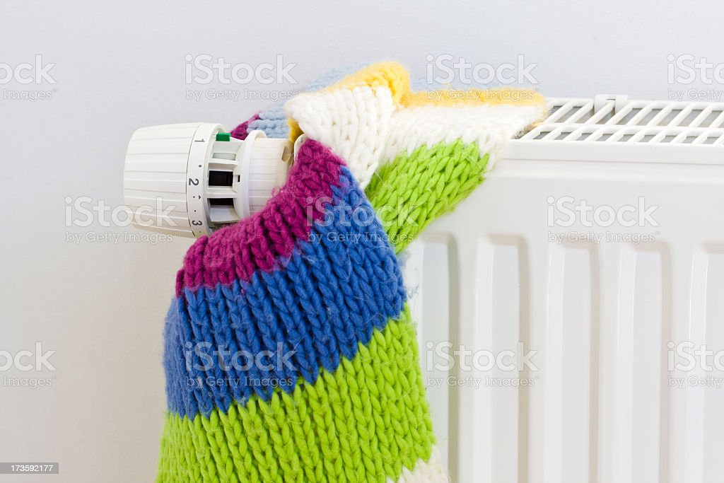 Energy saving concept with a knit scarf tied to a radiator royalty-free stock photo
