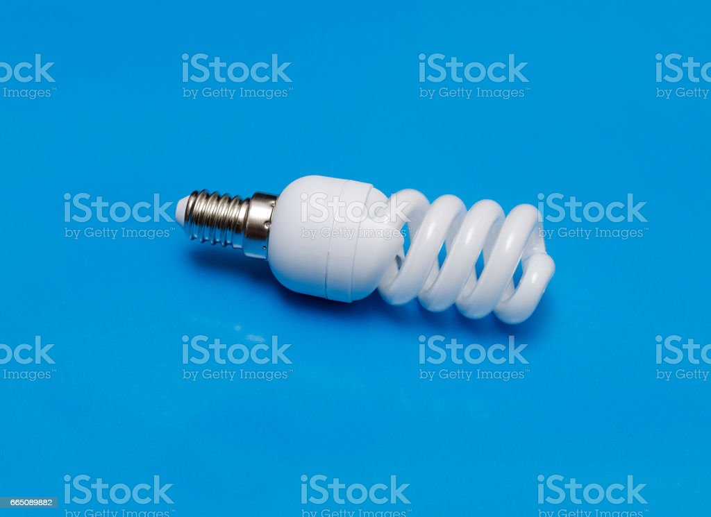 Energy saving  lamp on turquoise background. stock photo