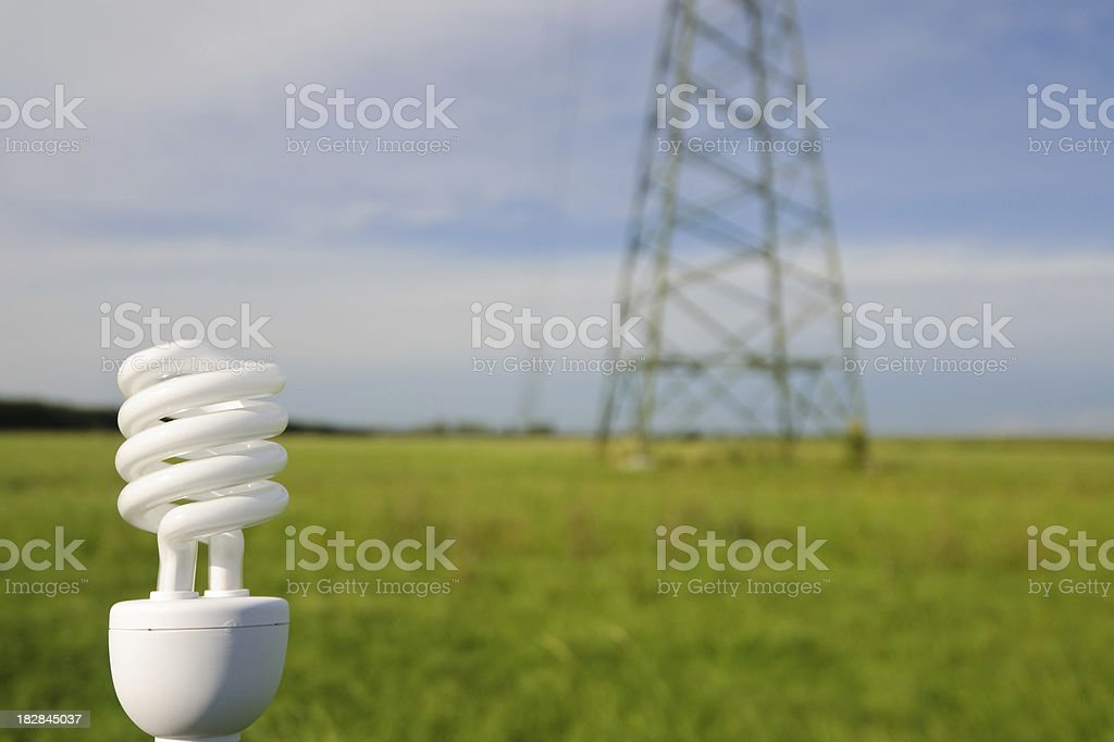 Energy saving lamp with powerline in background royalty-free stock photo