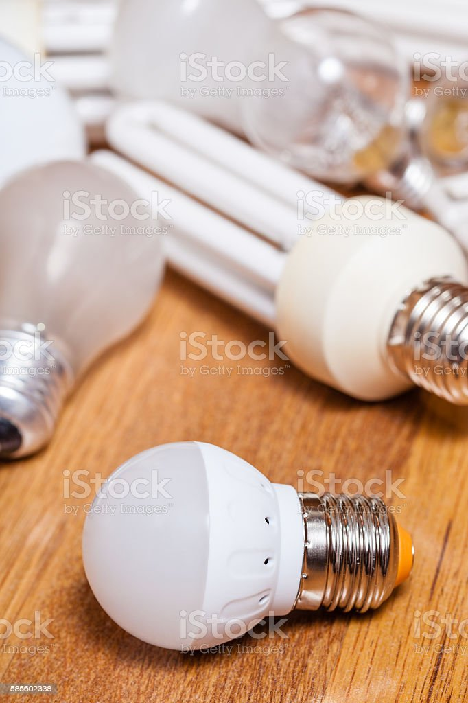 energy saving LED lamp and pile of old bulbs stock photo