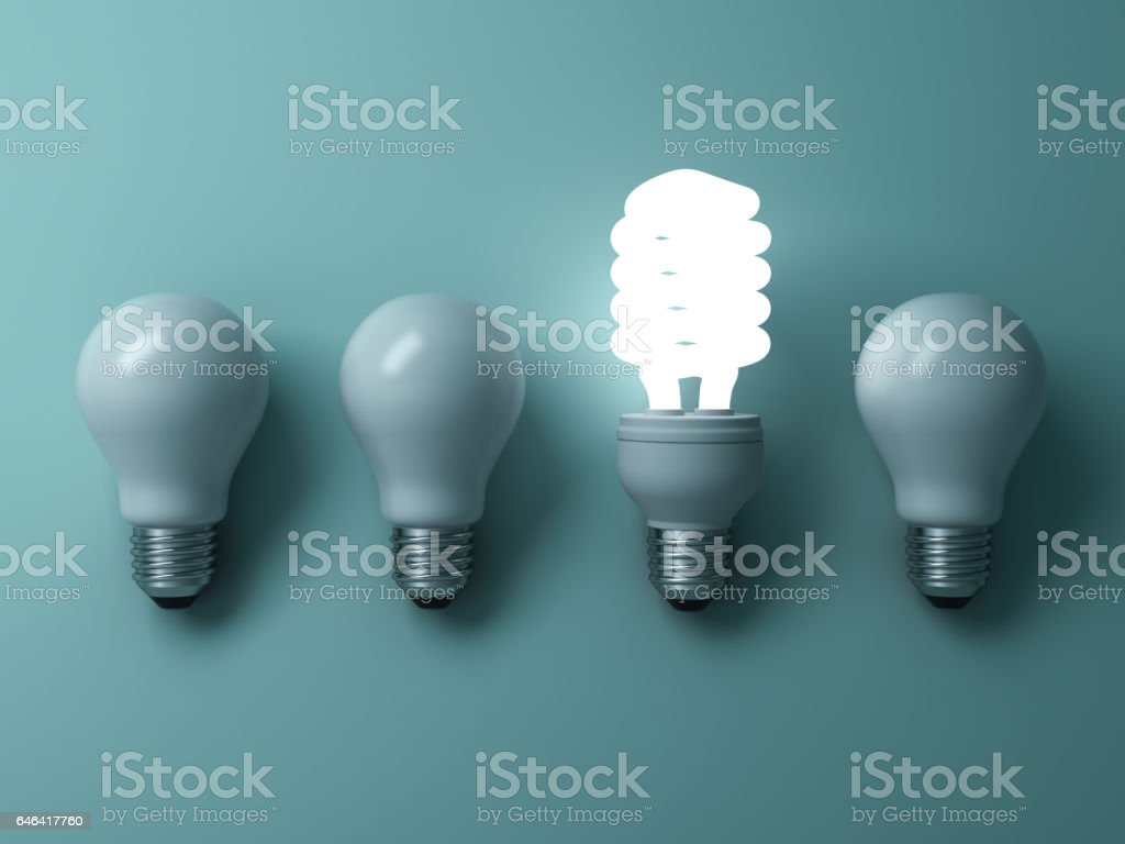 Energy saving light bulb , one glowing compact fluorescent lightbulb standing out from unlit incandescent bulbs on green background , individuality and different creative idea concepts stock photo