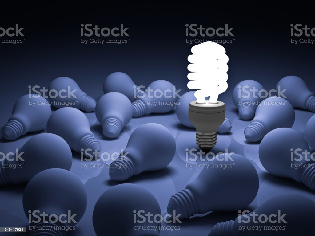 Energy saving light bulb , one glowing compact fluorescent lightbulb standing out from unlit incandescent bulbs on blue background , individuality and different creative idea concepts stock photo