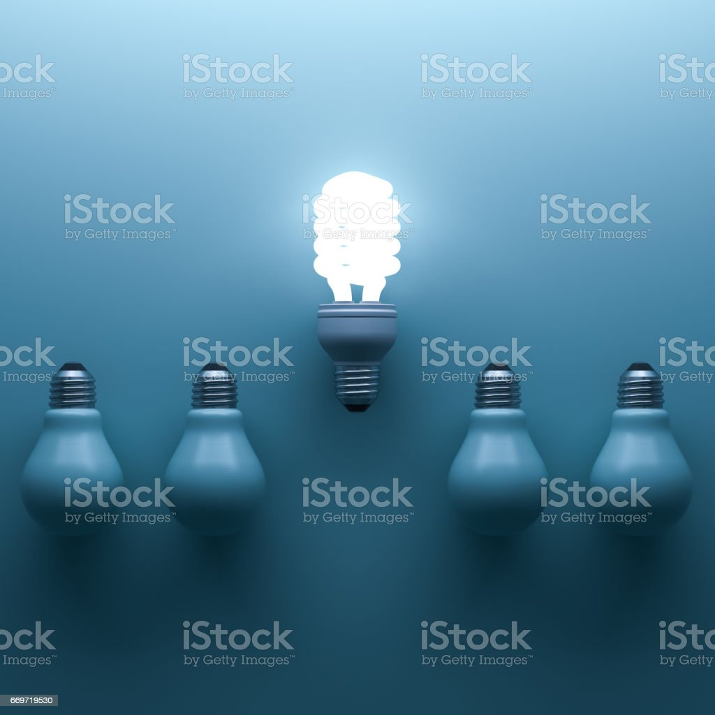 Energy saving light bulb , one glowing compact fluorescent lightbulb standing out from unlit incandescent bulbs on cyan background , individuality and different creative idea concepts . 3D rendering stock photo
