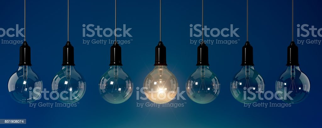 Energy Saving Light Bulb Standing Out From The Crowd Over Blue Background: Energy Efficiency and Standing Out From The Crowd Concept stock photo