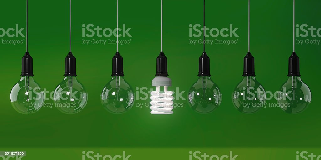 Energy Saving Light Bulb Standing Out From The Crowd Over Green Background: Energy Efficiency and Standing Out From The Crowd Concept stock photo