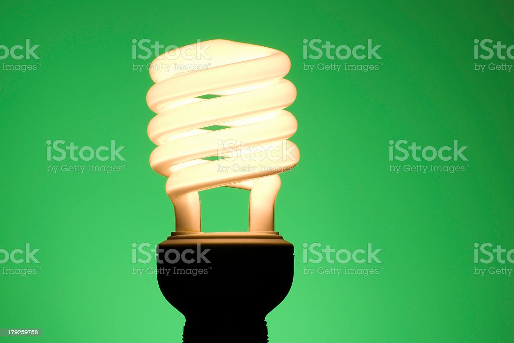 Energy saving swirl light bulb lit up against green royalty-free stock photo