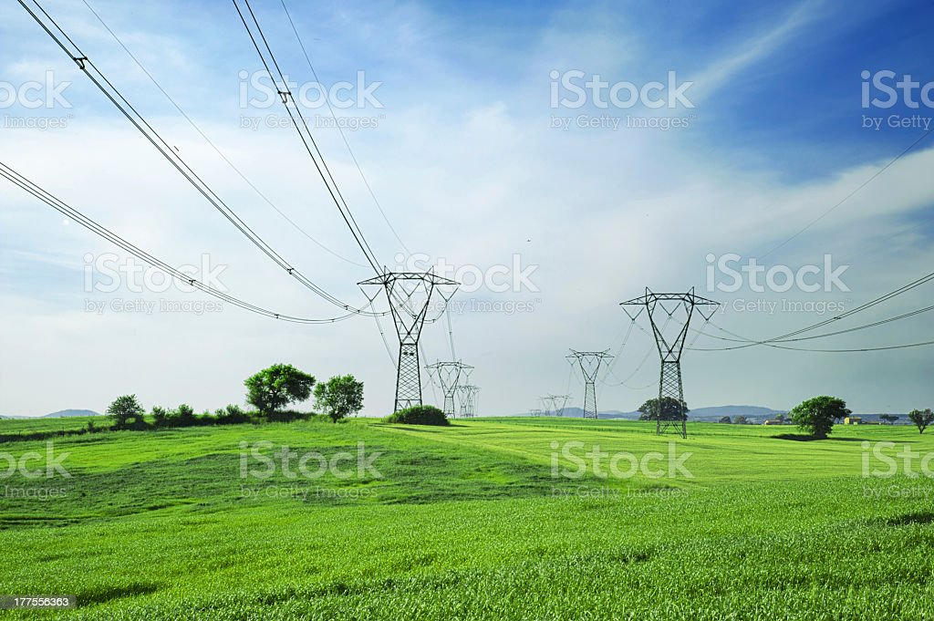 Energy towers and power lines over a green grassy field stock photo